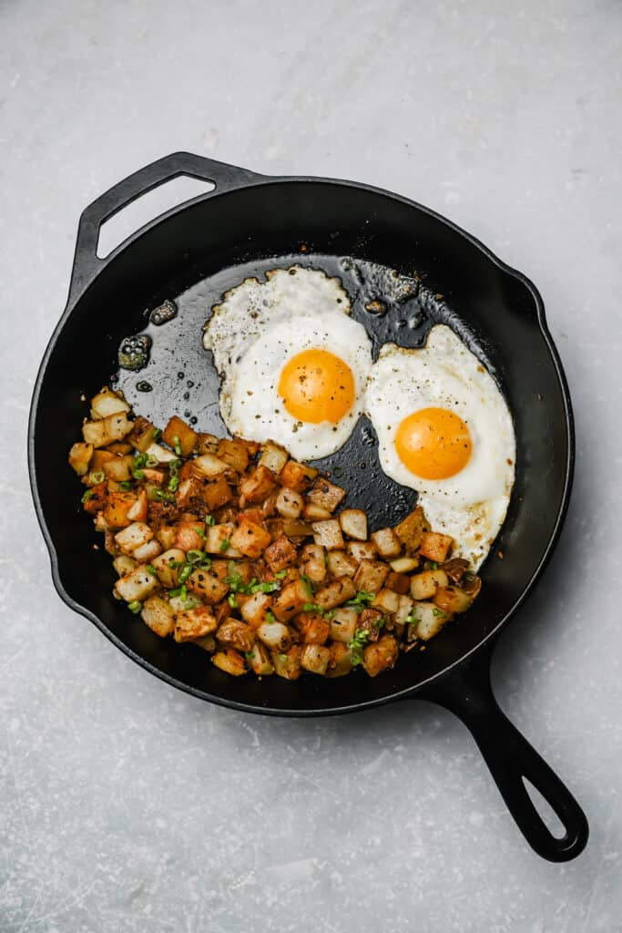 Fried potatoes and onion with fried eggs in a cast iron skillet