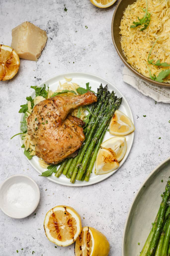 Grilled chicken with asparagus and lemon on a plate