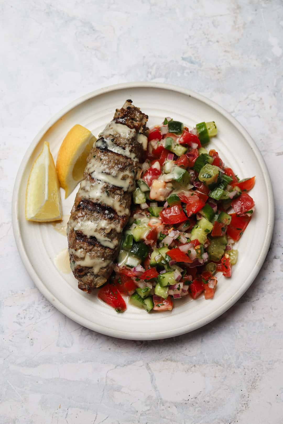 Beef kebab with Israeli salad on a plate