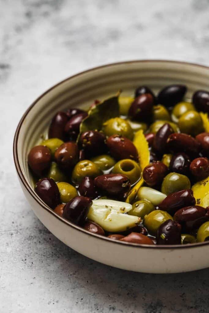 Kalamata and green olives in a bowl with garlic and lemon
