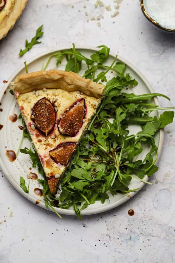 Savory fig tart on a plate with arugula salad and balsamic