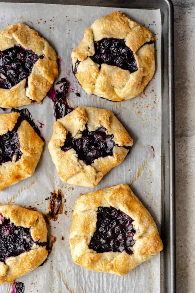 Individual blueberry galettes on a baking sheet